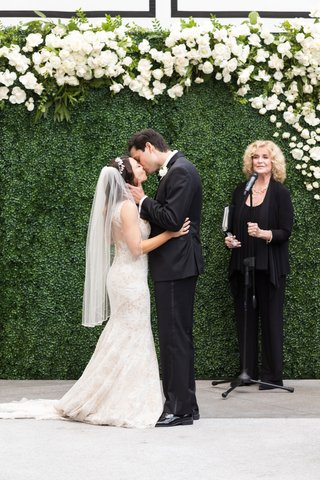 woman-officiant-wedding-ceremony-kiss-the-bride-veil-green-hedge-wall-white-flowers