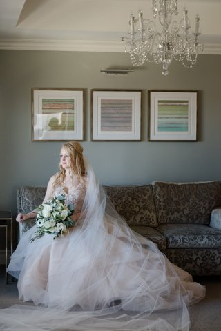 bride-in-martina-liana-layered-blush-ballgown-sitting-on-sofa-carrying-bouquet-of-ivory-and-greenery
