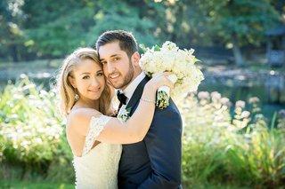 bride-holding-wedding-bouquet-with-hands-on-groom-shoulders-off-shoulder-strap-anne-barge-gown