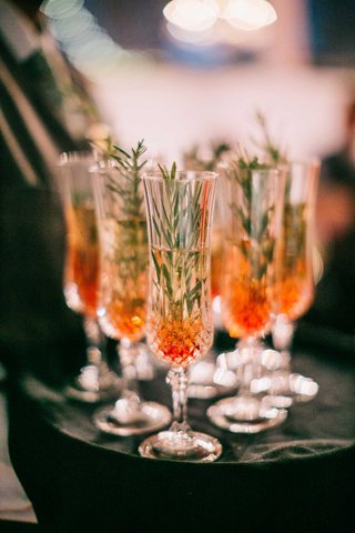 holiday-wedding-toast-champagne-flutes-with-champagne-red-berry-and-rosemary-sprig