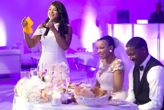 maid-of-honor-with-white-katie-may-dress-giving-toast-in-room-with-purple-uplighting