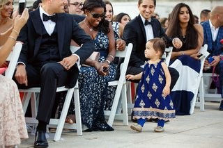 a-little-toddler-in-a-pakistani-dress-of-blue-and-gold-walks-down-aisle-during-ceremony