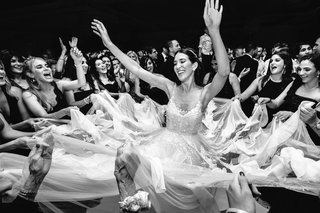 black-and-white-photo-of-bride-hands-on-dance-floor-friends-grabbing-pieces-of-wedding-dress-skirt