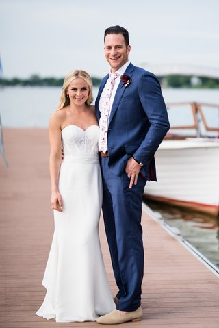 bride-in-strapless-lihi-hod-bridal-gown-with-groom-in-blue-suit-floral-tie-on-dock-of-lake-mendota