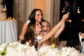 bride-sitting-down-at-reception-taking-selfie-with-bridesmaids-on-selfie-stick