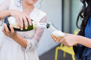 bride-in-white-robe-getting-ready-pouring-champagne-bottle-into-bridesmaid-glass
