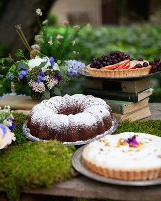a-fruit-tart-on-stack-of-books-bundt-cake-and-cream-pie-at-outdoor-wedding-reception