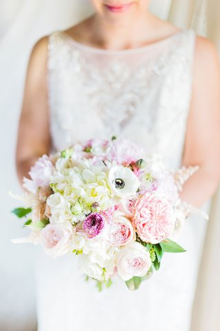 bride-in-high-neck-beaded-wedding-dress-holding-bouquet-white-anemone-garden-rose-peony-flowers