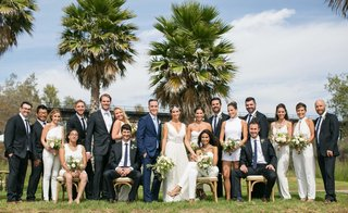 bride-in-white-v-neck-sheath-dress-groom-in-navy-blue-suit-bridesmaids-in-jumpsuits-and-groomsmen