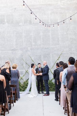 wedding-ceremony-concrete-no-aisle-runner-greenery-at-altar-on-wall-criss-cross-pattern-string-light