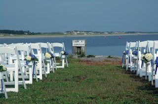 white-ceremony-chairs-on-grass-lawn-in-front-of-bay