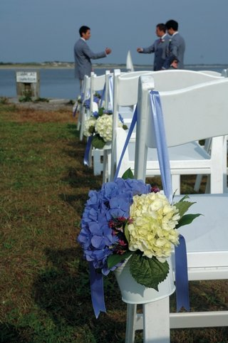 white-ceremony-chair-with-blue-hydrangeas-in-pail