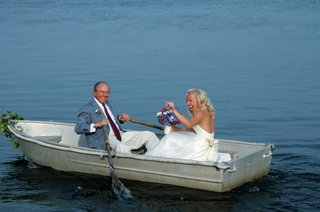 father-of-bride-rows-oars-of-rowboat-with-bride-in-boat