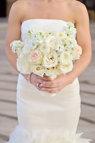 bride-holds-a-bouquet-of-blush-and-ivory-roses-and-other-small-flowers
