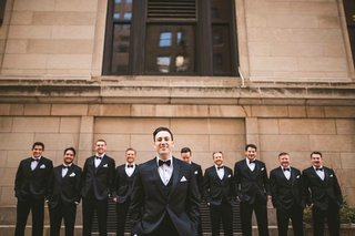 wedding-photo-groom-in-tuxedo-bow-tie-white-pocket-square-groomsmen-in-matching-tuxedo-suits