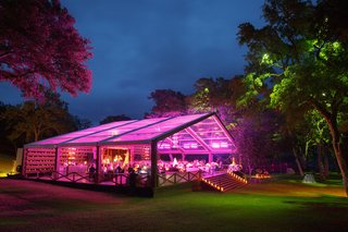 outdoor-wedding-reception-wood-structure-with-open-side-and-clear-ceiling-is-lit-by-fuchsia-lighting