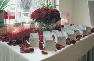 escort-card-table-with-red-roses-and-hurricane-candles