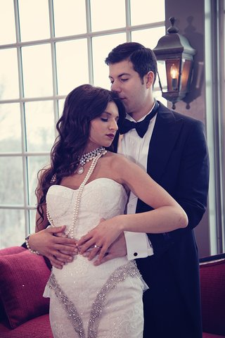 groom-in-black-tuxedo-hugs-bride-in-strapless-lace-dress-with-crystal-details