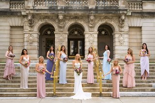 bridesmaids-in-pink-champaign-blue-and-periwinkle-standing-on-steps
