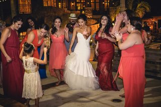 a-bride-her-bridesmaids-in-coral-and-red-dresses-and-the-flower-girl-in-white-lace-dance-reception