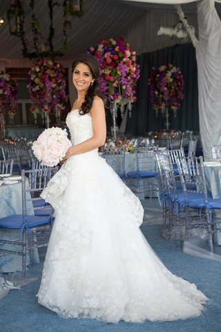 bride-in-a-strapless-monique-lhuillier-dress-with-floral-appliques-holds-a-bouquet-of-light-flowers