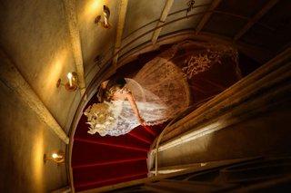 bride-in-lace-monique-lhuillier-wedding-dress-red-carpet-spiral-staircase-portrait