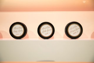 unique-escort-card-ideas-hockey-puck-with-gold-calligraphy-table-numbers-guest-names