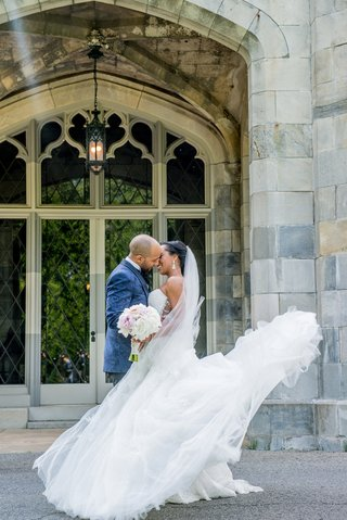 bride-and-groom-kiss-during-first-look-wedding-dress-blows-around-in-wind