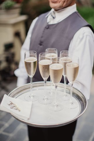 server-in-grey-vest-and-bow-tie-holding-champagne-flutes-and-monogram-napkins-on-silver-tray