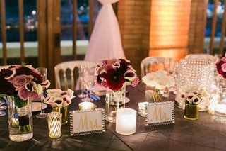head-table-with-mr-and-mrs-signs-in-crystal-frames-low-flower-centerpieces-roses-calla-lilies-purple
