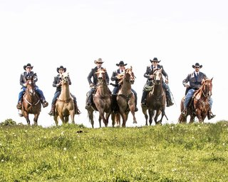 groom-and-groomsmen-in-cowboy-hats-galloping-over-lawn
