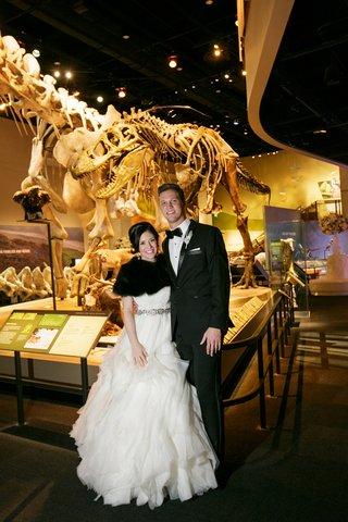 bride-in-lazaro-ball-gown-black-fur-shrug-groom-in-tuxedo-dinosaur-fossils-museum-wedding