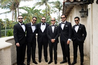 groom-in-sunglasses-and-bow-tie-tuxedo-with-groomsmen-in-matching-outfits-on-balcony