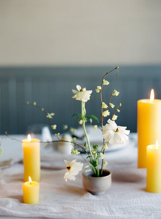 yellow-pillar-candles-mini-pillar-candles-ceramic-bud-vase-with-japanese-ranunculus