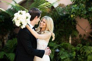 bride-in-inbal-dror-wedding-dress-holding-white-wedding-bouquet-hugging-groom-in-tuxedo-bel-air