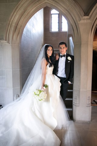 bride-in-monique-lhuillier-wedding-dress-peplum-tulle-long-train-veil-white-bouquet-groom-in-tuxedo