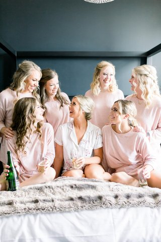 bride-and-bridesmaids-getting-ready-in-matching-pajamas-with-glasses-of-champagne
