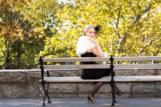 bride-in-a-black-oscar-de-la-renta-dress-feather-headpiece-white-fur-stole-gold-heels-on-bench