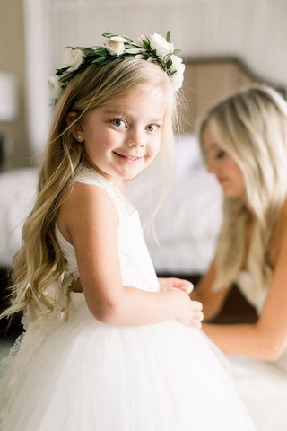 flower-girl-in-white-ball-gown-with-lace-straps-long-blonde-hair-flower-crown-greenery-white-roses