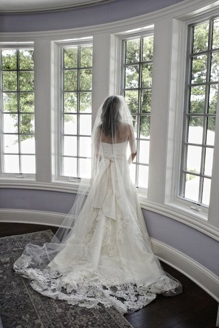 bride-with-lace-gown-standing-at-bay-window