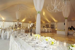 tent-wedding-with-white-table-decorations-and-drapery