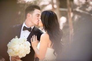 groom-in-bow-tie-holds-garden-rose-bouquet-while-kissing-bride