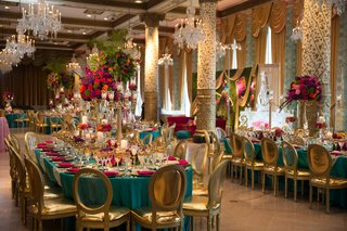 turquoise-pink-gold-tablescape-area-varying-levels-of-floral-arrangements-candles-gold-chairs