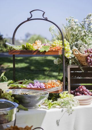 fresh-fruit-station-spread-grapes-leaves-white-wildflowers-wooden-plates-food-reception