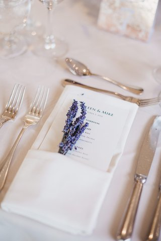 wedding-reception-place-setting-with-a-printed-menu-and-sprigs-of-lavender-tucked-into-ivory-napkin