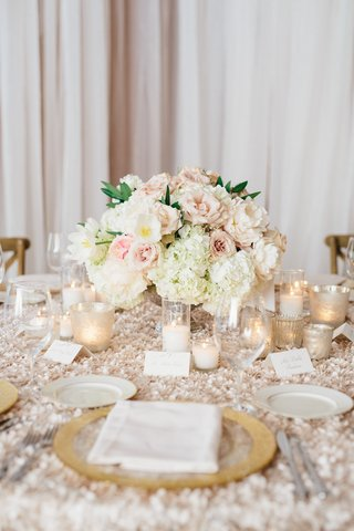 textured-linens-with-gold-charger-plate-candle-votives-and-low-flower-arrangement-centerpieces