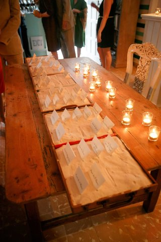 wood-table-with-candles-escort-cards-in-boxes-filled-with-white-sand-destination-wedding