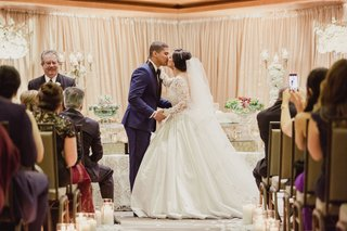 traditional-wedding-ceremony-bride-in-ball-gown-pnina-tornai-kiss-chairs-guests-taking-photos