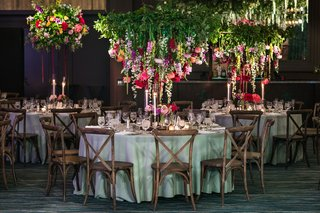 wedding-reception-table-with-vineyard-chairs-inverted-floral-arrangement-with-greenery