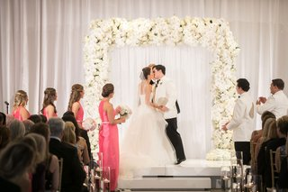 bride-and-groom-newlywed-first-kiss-bridesmaids-hot-pink-white-flower-decor-ballroom-ceremony-decor